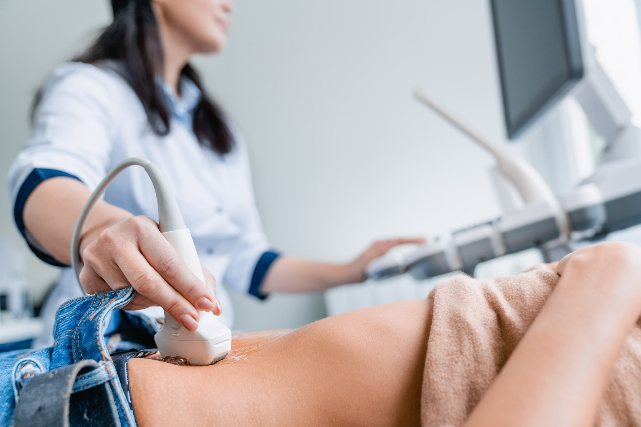 Close up of female doctor doing ultrasound probe on patient stomach in medical clinic